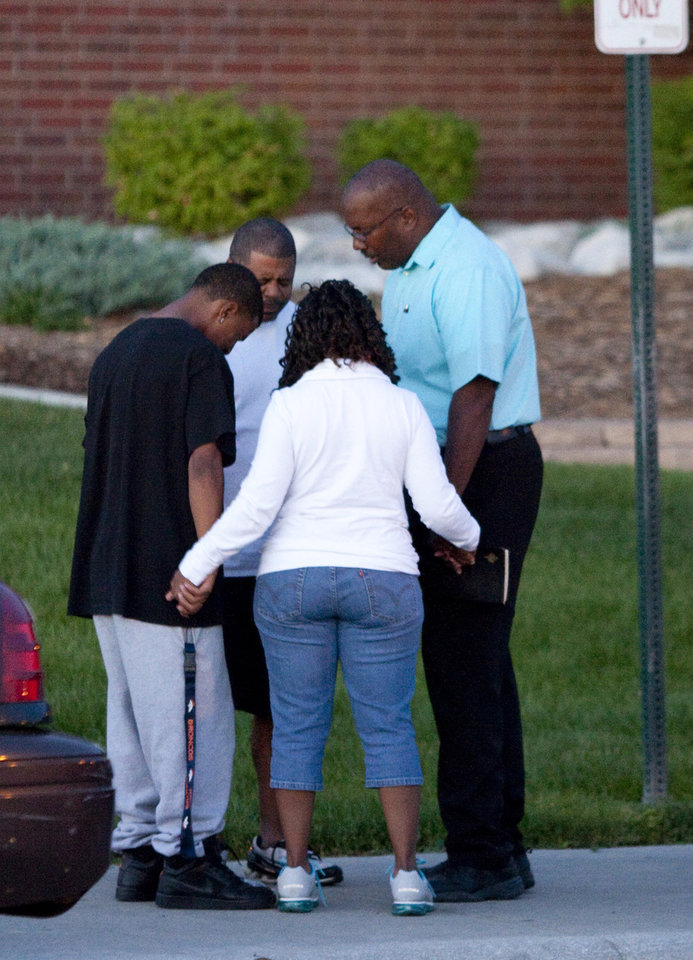 Photo - A small group prays outside Gateway High School where witness were brought for questioning Friday, July 20, 2012 in Aurora, Colo.  A gunman wearing a gas mask set off an unknown gas and fired into the crowded movie theater killing 12 people and injuring at least 50 others, authorities said. (AP Photo/Barry Gutierrez)  ORG XMIT: COBG109