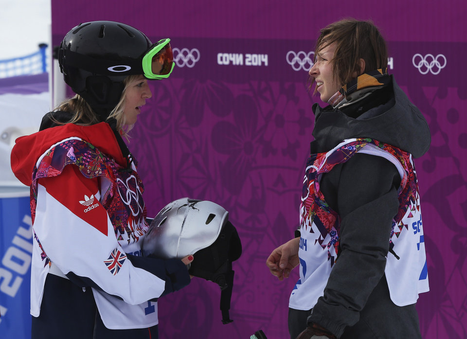 Photo - Britain's Jenny Jones holds the smashed helmet of Czech Republic's Sarka Pancochova, right, after Pancochova crashed heavily during the women's snowboard slopestyle final at the 2014 Winter Olympics, Sunday, Feb. 9, 2014, in Krasnaya Polyana, Russia. (AP Photo/Sergei Grits)