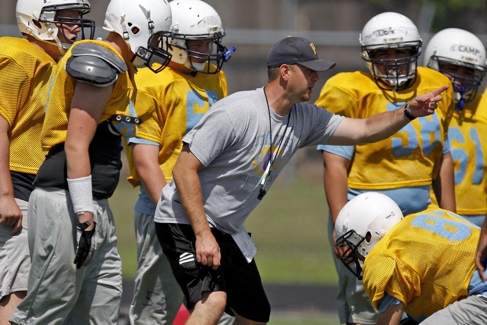 Photo - HIGH SCHOOL FOOTBALL: Putnam CIty West coach Rocky Martin works with his players during football practice at Putnam City West High School in Oklahoma City, Friday, May 18, 2012. Photo by Bryan Terry, The Oklahoman