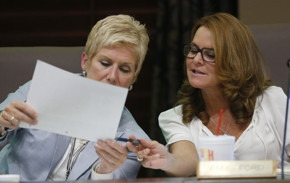 Photo -  Above: Janet Barresi, left, state schools superintendent, looks over a paper with board member Amy Ford, right, during a state Board of Education meeting in Oklahoma City. AP photo    -  AP