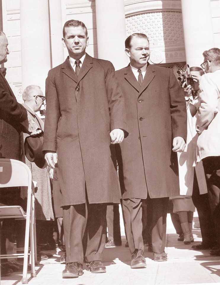 Gov. George Nigh, left, escorts a winking Henry Bellmon to the platform for Bellmon's swearing in ceremony on Jan. 14, 1963.  OKLAHOMAN ARCHIVE PHOTO