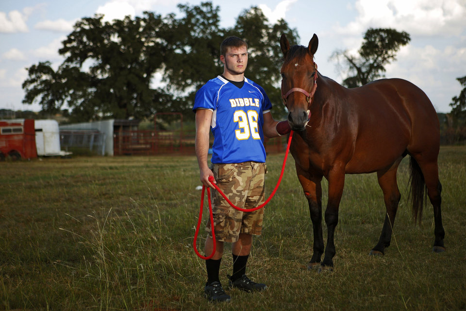 Photo - Dibble football player Tazden Jevons, who breaks horses, stands with Dreamer in Dibble, Okla., Oct. 2, 2013. Photo by Bryan Terry, The Oklahoman