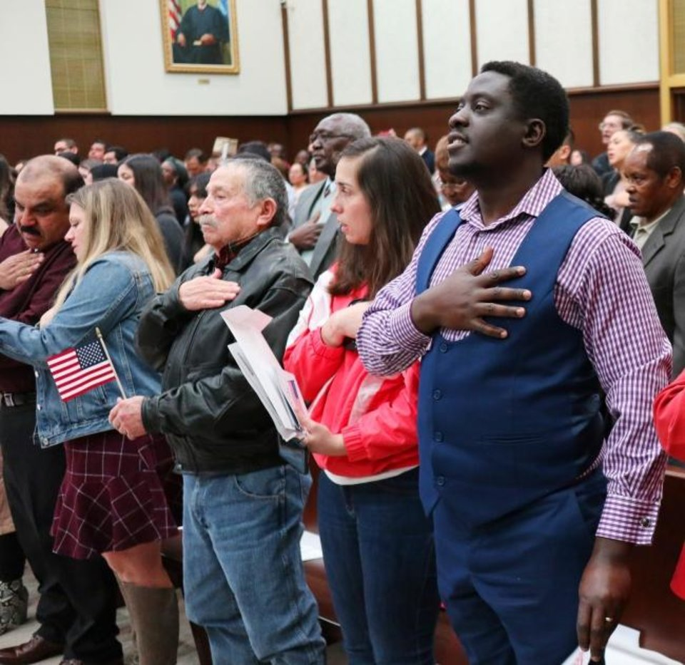 Photo -  Nelson Etinzock, from Cameroon, takes part in the Pledge of Allegiance at the naturalization ceremony at the District Court for the Western District of Oklahoma, Friday, February 28, 2020.  [Photo by Doug Hoke/The Oklahoman]
