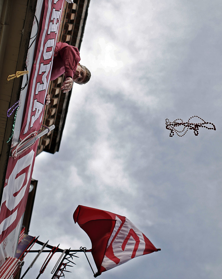 Photo - A man throws beads from a balcony on Bourbon Street in the French Quarter, Thursday, Jan. 2, 2014 in New Orleans. Photo by Sarah Phipps, The Oklahoman