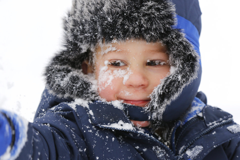 Photo - Owen has a face full of snow after his brother, Bennett, tossed an arm full of snow at him, while at the park with their grandmother, Jeanne Hapton, at Bickham Rudkin Park in Edmond, Wednesday, February 5, 2020.  [Photo by Doug Hoke/The Oklahoman]