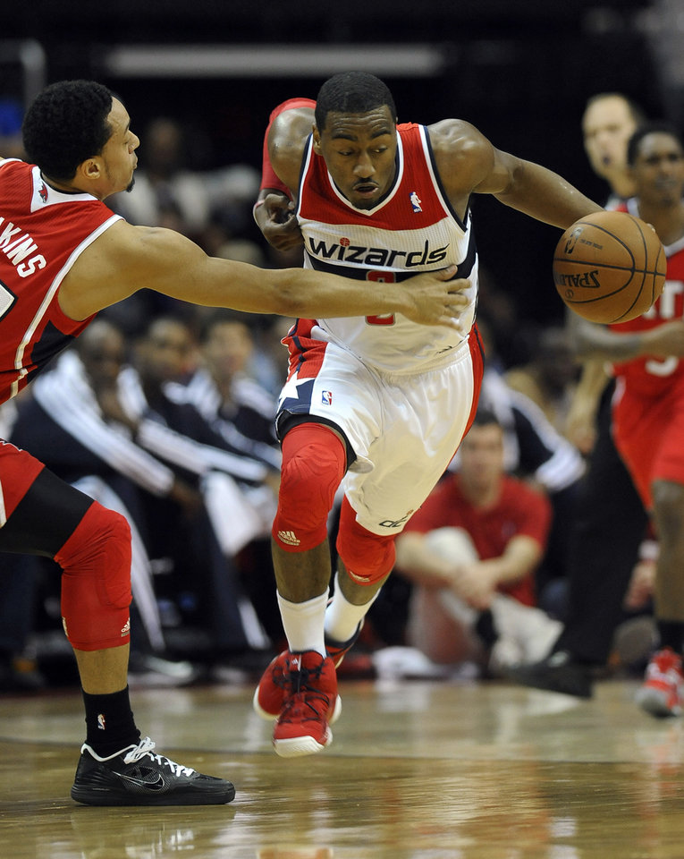 Washington Wizards guard John Wall, right, dribbles past Atlanta Hawks guard John Jenkins during the first half of their NBA basketball game on Saturday, Jan. 12, 2013, in Washington. Wall had been sidelined since being diagnosed with a stress injury to his left kneecap in September. (AP Photo/Richard Lipski)