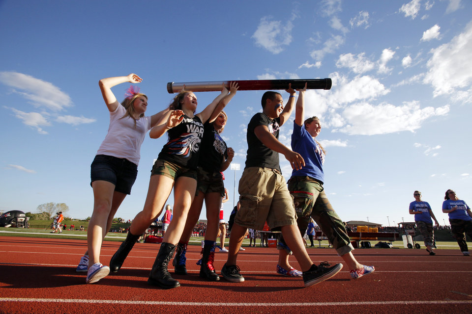 Fans from both schools carry the spirit stick around the stadium as Moore High School and Westmoore play football on Friday, Aug. 31, 2012 in Moore, Okla.  Photo by Steve Sisney, The Oklahoman