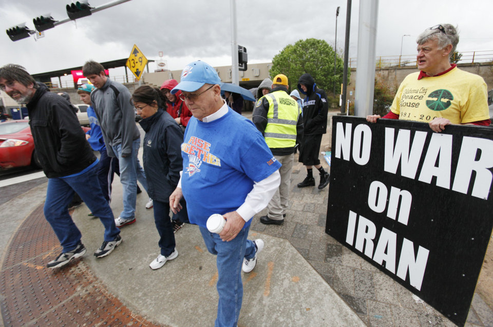 Photo - Thunder fans walk by Nathaniel Batchelder who was taking part in a protest at Reno and E.K. Gaylord on the drive home Wednesday, March 21, 2012. Photo by Doug Hoke, The Oklahoman