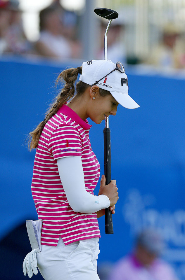 Photo - Azahara Munoz, of Spain, looks down after missing a birdie putt on the 18th hole during the final round of the LPGA Founders Cup golf tournament on Sunday, March 23, 2014, in Phoenix.  Munoz finished tied for second place at 18-under par, one shot behind the winner, Karrie Webb. (AP Photo/Ross D. Franklin)