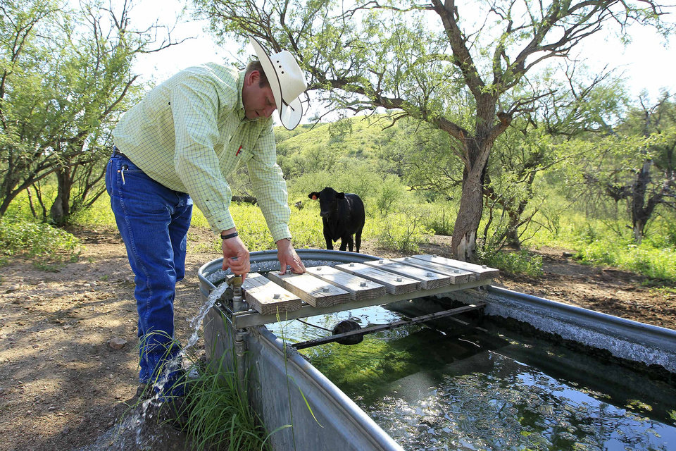 Photo - In this Friday, Aug. 10, 2012 photo, rancher Dan Bell, who leases a 35,000-acre cattle ranch along the border between the United States and Mexico, checks out part of the property in Nogales, Ariz., including a watering station for his cattle, which is also user-friendly for illegal immigrants that walk the land. (AP Photo/Ross D. Franklin)