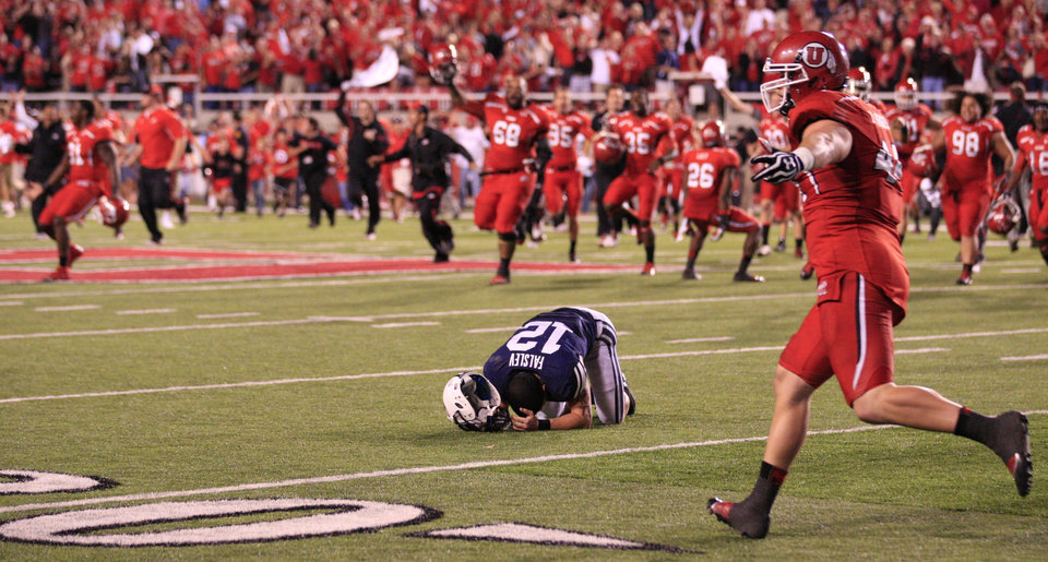 Photo -   A dejected BYU's JD Falslev (12) drops to the turf as Utah players celebrate on the field after a missed field goal at the end of their NCAA football game Saturday, Sept. 15, 2012, in Salt Lake City. Utah defeated BYU 24-21. BYU's Riley Stephenson's 36-yard attempt with no time left clanked off the left upright, sending the frenzied crowd back on the field for good to celebrate the upset. (AP Photo/Rick Bowmer)