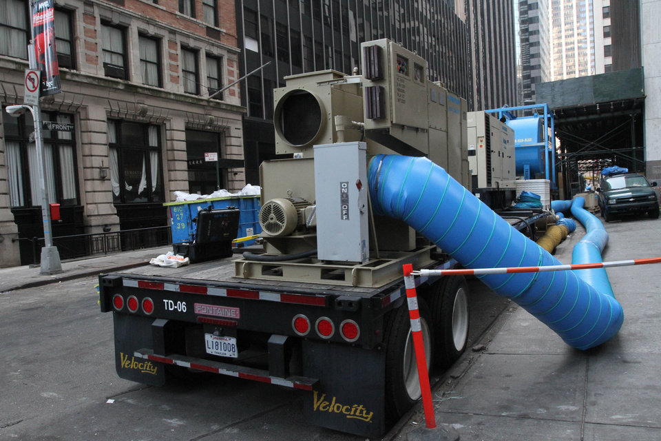 Photo -   In this Friday, Nov. 23, 2012 photo, a dehumidifier, parked on Front Street near Wall Street in New York, blows dry air into the basement of a nearby building. Parts of lower Manhattan's Financial District are still laboring to recover nearly a month after Superstorm Sandy. A real estate consulting firm says that of the nearly 50 office buildings shut down after Sandy buffeted the Financial District, about half have reopened. Some of the others that are home to large financial and law firms still could be closed for weeks, if not months. (AP Photo/Tina Fineberg)