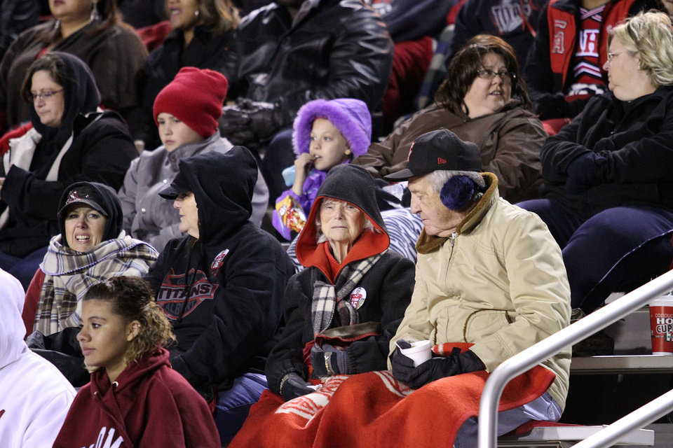 Photo - Carl Albert High School football fans bundled up against the chilly weather during the Carl Albert Titans - Ardmore Tigers football game Friday night at Jim Harris stadium in Midwest City. PHOTO BY HUGH SCOTT, FOR THE OKLAHOMAN