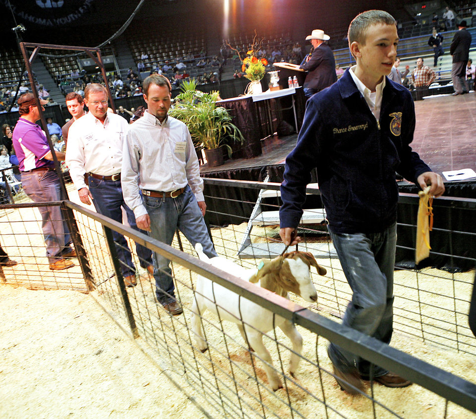 Chance Greenroyd of Noble FFA leads his reserve grand champion goat during the Oklahoma Youth Expo Sale of Champions at State Fair Park. PHOTO BY JOHN CLANTON, THE OKLAHOMAN