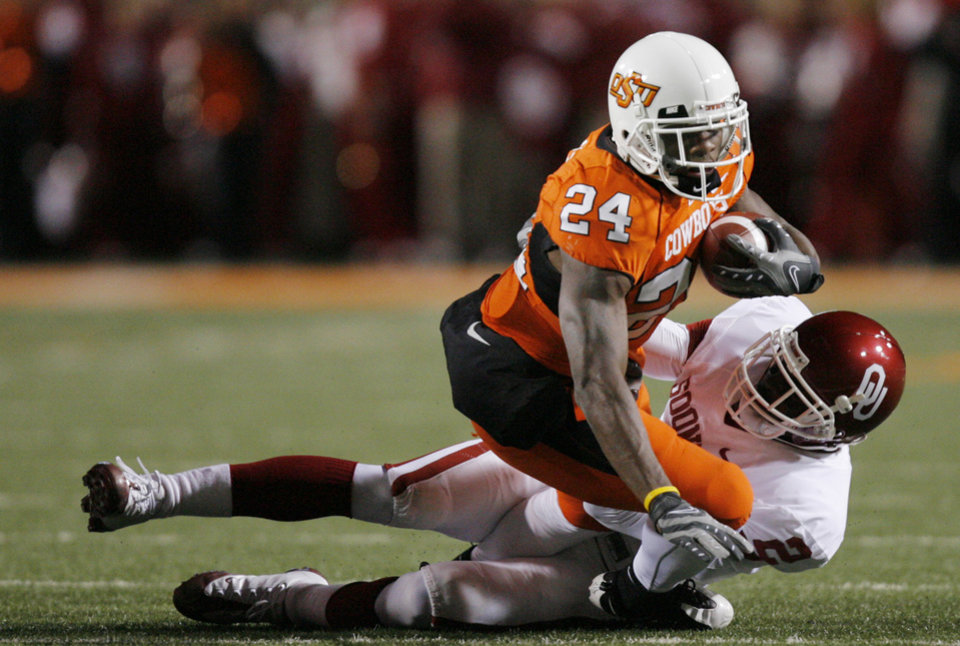 Sooner Brian Jackson brings down Kendall Hunter of Oklahoma State during the first half of the college football game between the University of Oklahoma Sooners (OU) and Oklahoma State University Cowboys (OSU) at Boone Pickens Stadium on Saturday, Nov. 29, 2008, in Stillwater, Okla. STAFF PHOTO BY CHRIS LANDSBERGER
