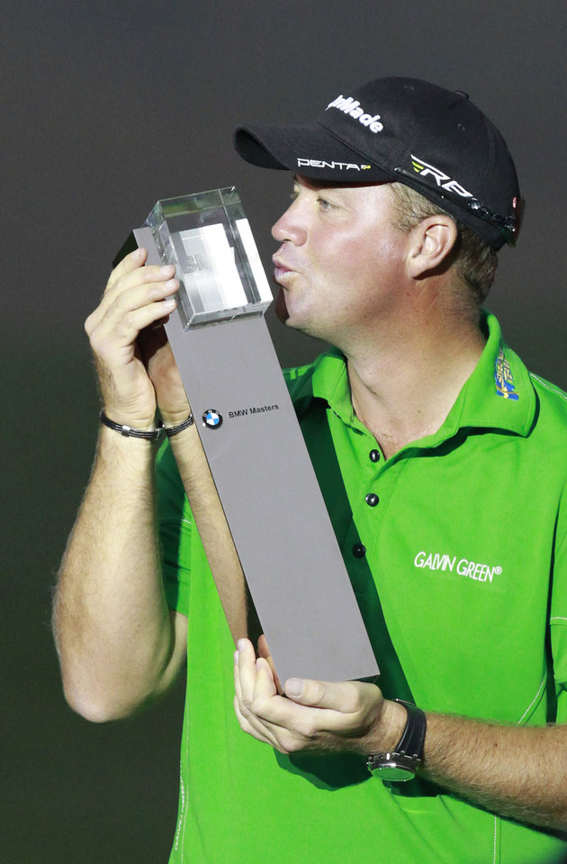 Photo -   Peter Hanson from Sweden kisses his champion trophy during the award ceremony of the Masters golf tournament in Shanghai, China on Sunday Oct. 28, 2012. (AP Photo/Eugene Hoshiko)