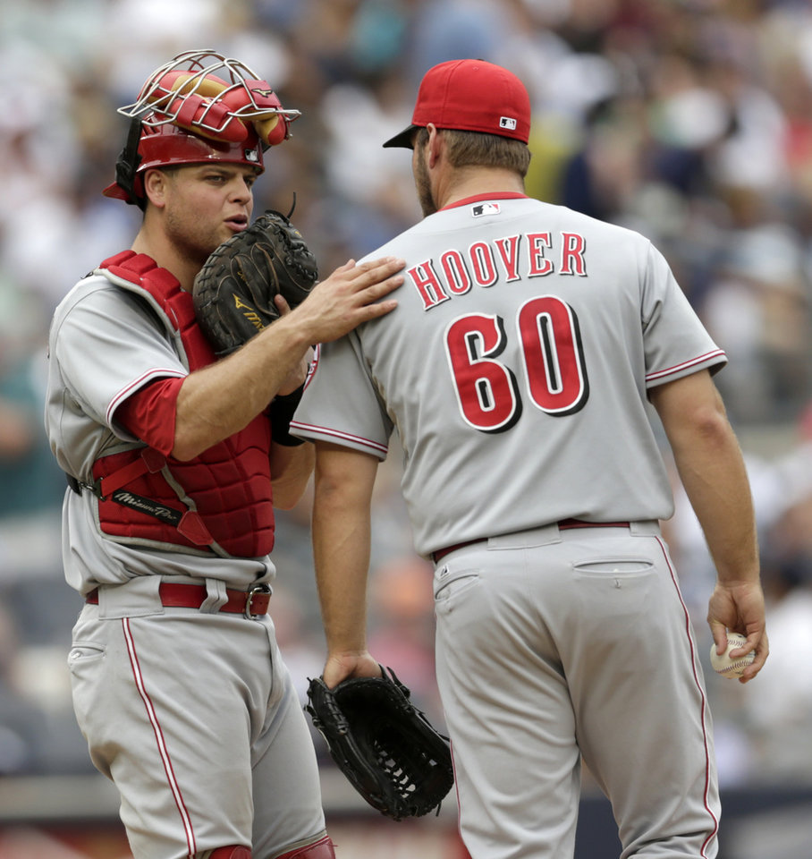 Photo - Cincinnati Reds catcher Devin Mesoraco, left, talks to relief pitcher J.J. Hoover during the sixth inning of a baseball game against the New York Yankees, Saturday, July 19, 2014, at Yankee Stadium in New York. (AP Photo/Julio Cortez)
