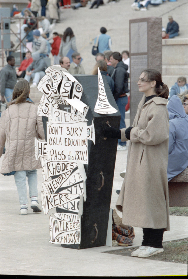 20th ANNIVERSARY OF HB-1017. Carolyn Meyer of Stillwater displays a coffin to illustrate her frustration over the state Legislature's failure to enact education reforms, at the state Capitol. April 16, 1990. Staff Photo by David McDaniel