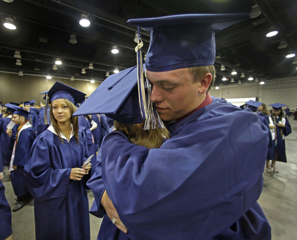 Photo - Southmoore High School senior Jake Spradling, hugs a classmate as they get ready to attend their commencement ceremony in Oklahoma City Saturday, May 25, 2013, five days after a tornado destroyed a large swath of their attendance area in Moore, Okla. Spradling's home was among those destroyed after a huge tornado roared through the Oklahoma City suburb Monday, flattening a wide swath of homes and businesses. (AP Photo/Charlie Riedel)