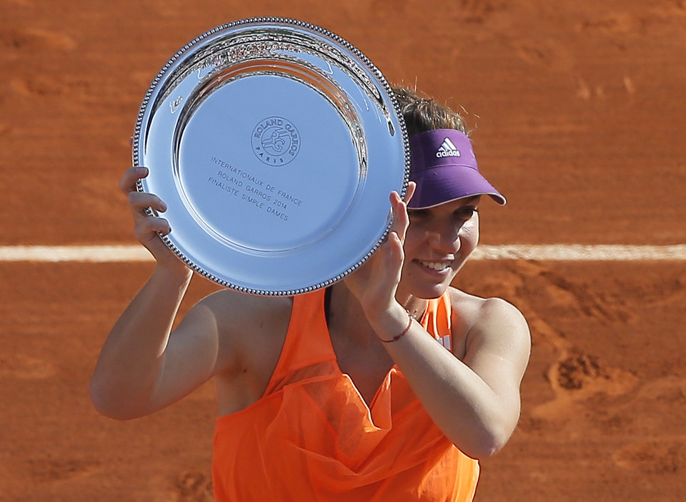 Photo - Romania's Simona Halep holds her trophy after losing to Russia's Maria Sharapova in the women's final of the French Open tennis tournament  at the Roland Garros stadium, in Paris, France, Saturday, June 7, 2014. Sharapova won 6-4, 6-7, 6-4.  (AP Photo/Michel Spingler)