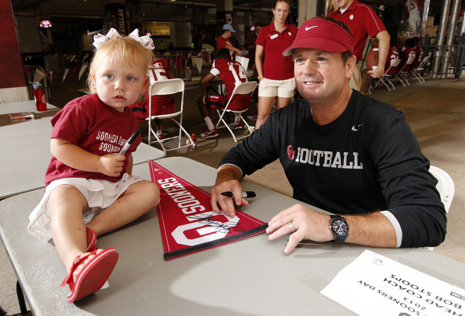 Photo - CHILD / CHILDREN / KIDS / COLLEGE FOOTBALL: Lilly Bittner, 2, from Oklahoma City, poses for a picture with head football coach Bob Stoops during fan appreciation day for the University of Oklahoma Sooner (OU) football team at Gaylord Family-Oklahoma Memorial Stadium in Norman, Okla., on Saturday, Aug. 3, 2013. Photo by Steve Sisney, The Oklahoman