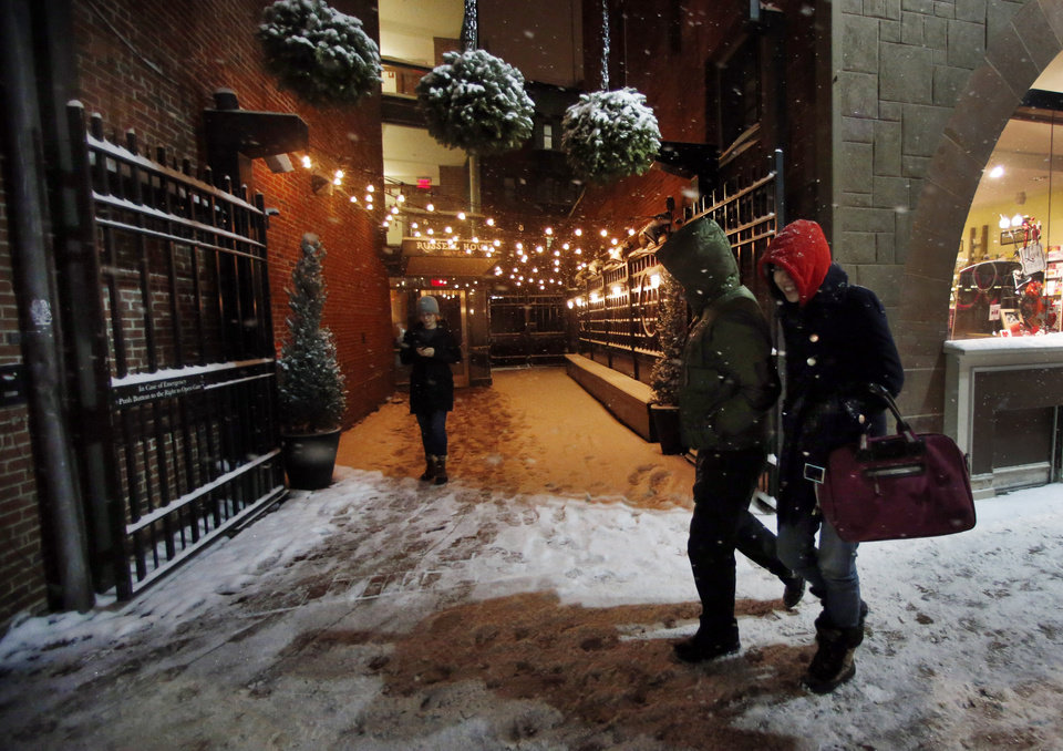 Photo - Pedestrians walk as snow falls in Harvard Square in Cambridge, Mass. Tuesday, Jan. 21, 2014. Heavy snow has been forecast and a blizzard warning was posted for portions of Massachusetts. (AP Photo/Elise Amendola)
