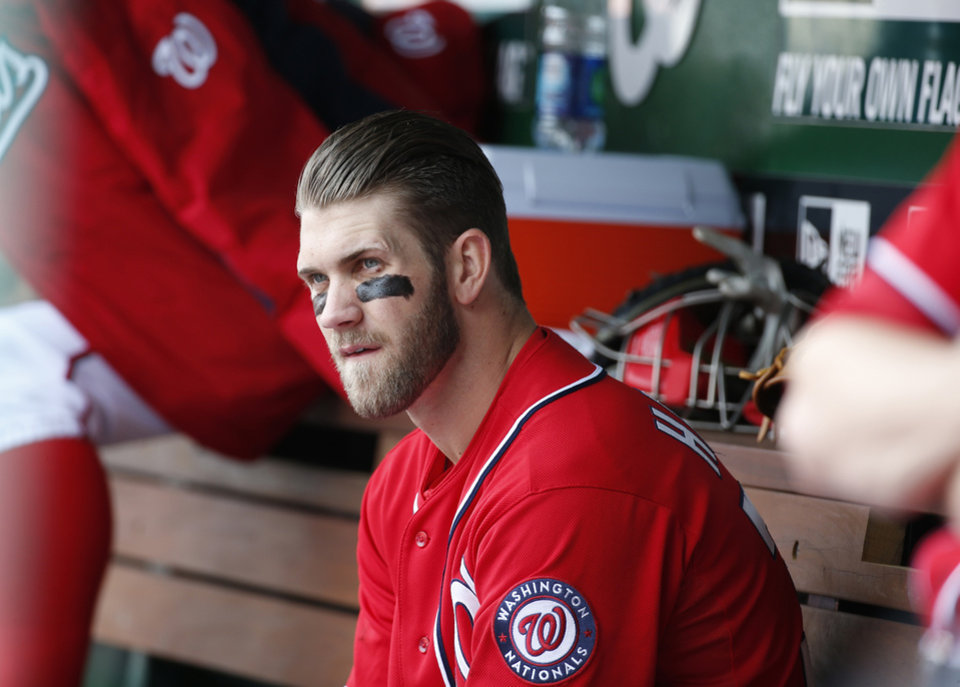 Photo - dWashington Nationals' Bryce Harper sits on the bench during the fourth inning of a baseball game against the St. Louis Cardinals at Nationals Park on Saturday, April 19, 2014, in Washington. The Cardinals won 4-3. Harper was pulled early from a game after Washington manager Matt Williams said the young outfielder didn't hustle. Harper was taken out after six innings. The 21-year-old Harper is a two-time All-Star known for his aggressive play. But in the sixth inning, he hit the ball to the mound, jogged to first and took a right turn to the dugout before getting halfway down the basepath. (AP Photo/Alex Brandon)