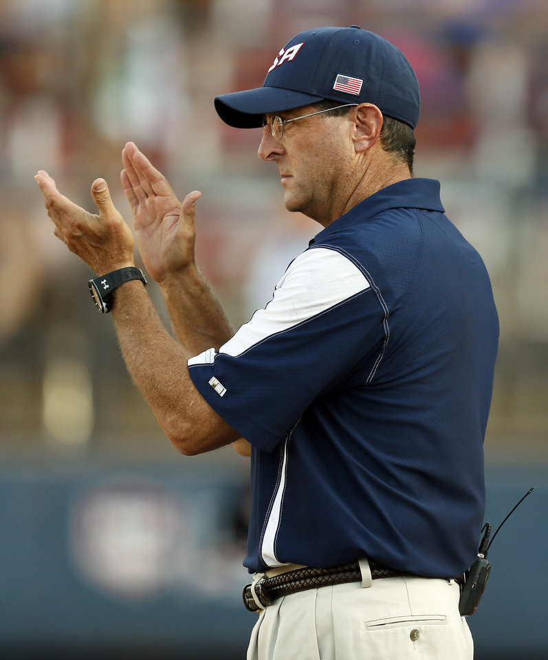 Photo - United States head coach Ken Eriksen applauds after a play during a game between Team USA and Canada in the World Cup of Softball at ASA Hall of Fame Stadium in Oklahoma City, Thursday, July 11, 2013. Team USA won 7-0 in 6 innings. Photo by Nate Billings, The Oklahoman