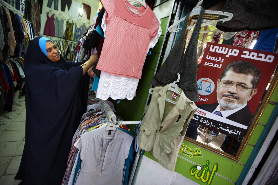 Photo -   An Egyptian woman looks at clothes next to a poster of Muslim Brotherhood presidential candidate, Mohammed Morsi with Arabic that reads,