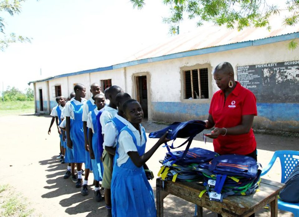 Photo - Maisha Project Executive Director Beatrice Williamson hands out backpacks to schoolchildren in Kenya. [PHOTO PROVIDED]