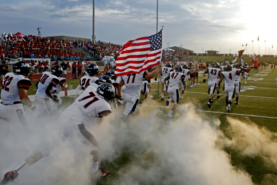 Photo - The Westmmoore team takes the field to play Southmoore before their high school football game in Moore, Okla., Friday, Sept. 13, 2013. Photo by Bryan Terry, The Oklahoman