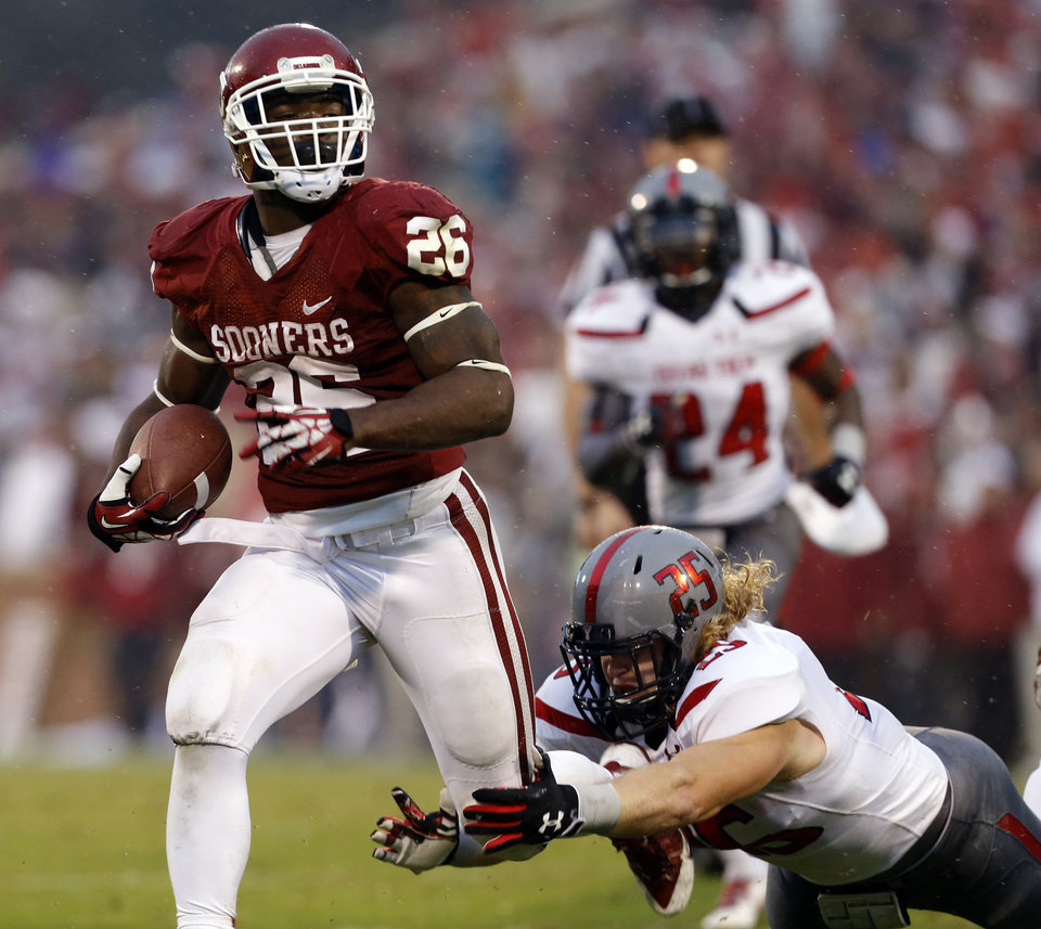 Oklahoma\'s Damien Williams (26) takes the ball to the two yard line after slipping the tackle of Texas Tech\'s Blake Dees (25) during a college football game where the University of Oklahoma Sooners (OU) defeated the Texas Tech Red Raiders 38-30 at Gaylord Family-Oklahoma Memorial Stadium in Norman, Okla., on Saturday, Oct. 26, 2013. Photo by Steve Sisney, The Oklahoman