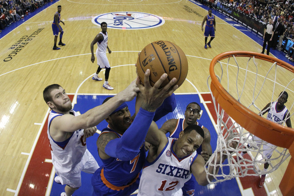 New York Knicks' Carmelo Anthony, center, battles for a rebound with Philadelphia 76ers' Spencer Hawes, left, and Evan Turner during the first half of an NBA basketball game on Saturday, Jan. 26, 2013, in Philadelphia. (AP Photo/Matt Slocum)