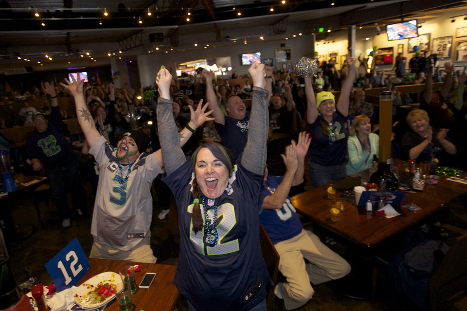 Photo - Seattle Seahawks fans Brittney Gutierrez, center, and her husband Mike Gutierrez, left, celebrate while watching Super Bowl XLVIII at Big Al's in Vancouver, Wash., Sunday, Feb. 2, 2014. Seattle defeated the Denver Broncos 43-8. (AP Photo/The Columbian, Steven Lane)