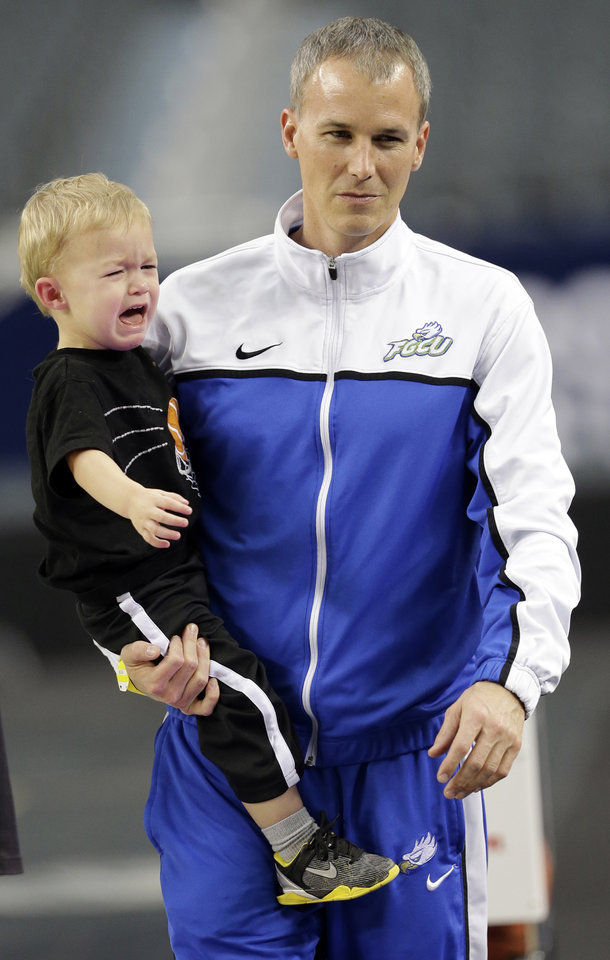 Florida Gulf Coast head coach Andy Enfield holds his son Marcum during practice for a regional semifinal game in the NCAA college basketball tournament, Thursday, March 28, 2013, in Arlington, Texas. Florida Gulf Coast faces Florida on Friday. (AP Photo/David J. Phillip)  ORG XMIT: TXMG123