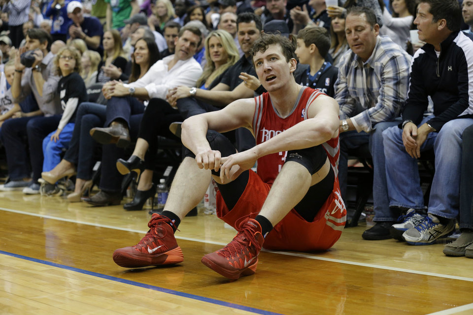 Photo - Houston Rockets center Omer Asik sits on the court after being charged with a foul during the fourth quarter of an NBA basketball game against the Minnesota Timberwolves in Minneapolis, Friday, April 11, 2014. The Timberwolves won 112-110. (AP Photo/Ann Heisenfelt)