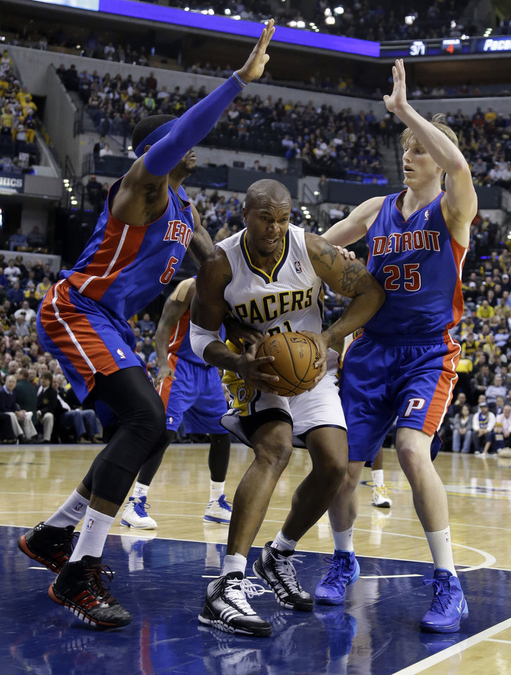 Photo - Indiana Pacers forward David West, center is trapped by Detroit Pistons forward Josh Smith, left, and forward Kyle Singler in the second half of an NBA basketball game in Indianapolis, Monday, Dec. 16, 2013. The Pistons defeated the Pacers 101-96. (AP Photo/Michael Conroy)