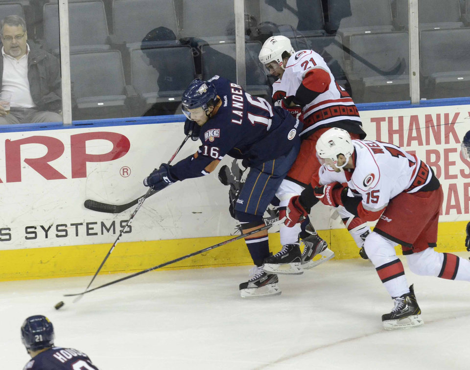 Photo - The Barons' Anton Lander, left, chases after the puck against the Checkers' Jeremy Welsh during Wednesday night's Game 3 at Time Warner Cable Arena. Photo by Robert Lahser, Charlotte Observer