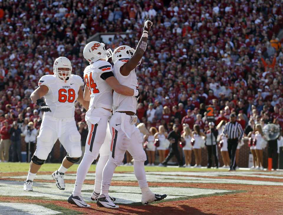 Photo - Oklahoma State's Joseph Randle (1), Austin Hays (84) and Oklahoma State's Lane Taylor (68) celebrate a Randle touchdown during the Bedlam college football game between the University of Oklahoma Sooners (OU) and the Oklahoma State University Cowboys (OSU) at Gaylord Family-Oklahoma Memorial Stadium in Norman, Okla., Saturday, Nov. 24, 2012. Photo by, Sarah Phipps The Oklahoman
