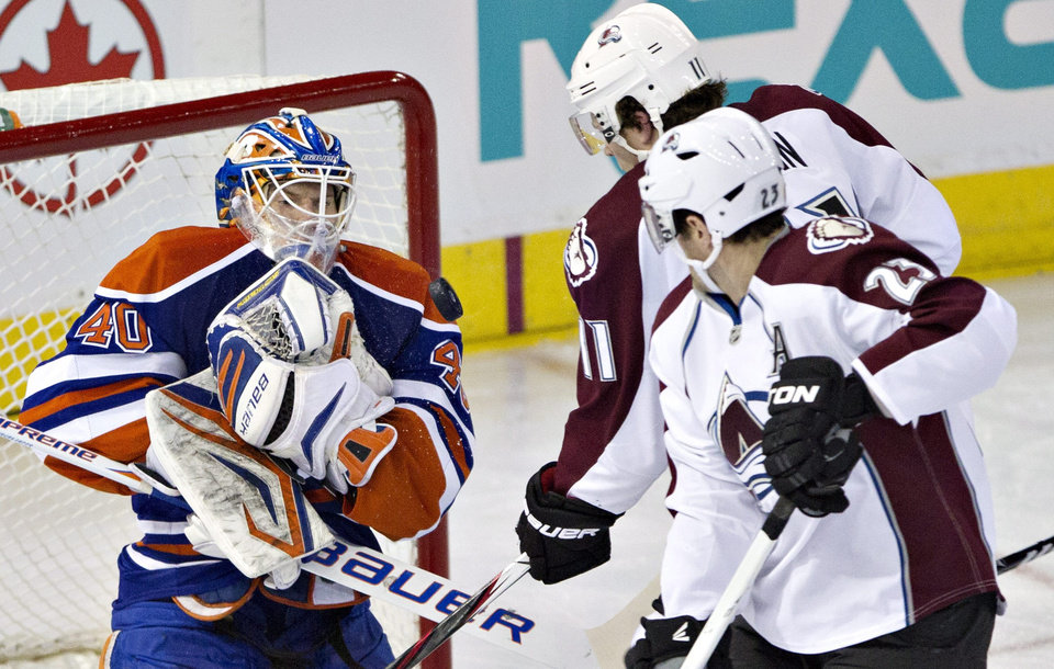 Edmonton Oilers goalie Devan Dubnyk makes the save as Colorado Avalanche's Jamie McGinn and Milan Hejduk (23) look for the rebound during the second period of their NHL hockey game, Monday, Jan. 28, 2013, in Edmonton, Alberta. (AP Photo/The Canadian Press, Jason Franson)