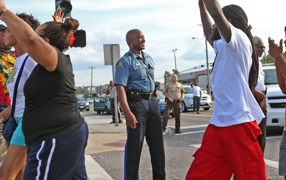Photo - Capt. Ronald Johnson of the Missouri Highway Patrol smiles at demonstrators march along West Florissant Avenue in Ferguson, Mo., on Thursday, Aug. 14, 2014. The Missouri Highway Patrol seized control of a St. Louis suburb Thursday, stripping local police of their law-enforcement authority after four days of clashes between officers in riot gear and furious crowds protesting the death of an unarmed black teen shot by an officer. (AP Photo/St. Louis Post-Dispatch, David Carson)