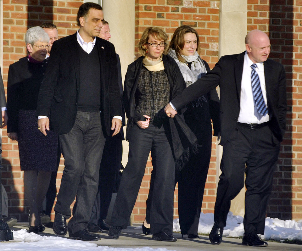 Former U.S. Rep. Gabrielle Giffords, center, holds hands with her husband, Mark Kelly, while exiting Town Hall at Fairfield Hills Campus in Newtown, Conn. after meeting with Newtown First Selectman Pat Llodra and other officials on Friday, Jan. 4, 2013. At far left is Lt. Gov. Nancy Wyman; behind Giffords to the left is U.S. Sen. Richard Blumenthal. Giffords also met with families of the victims of the Sandy Hook Elementary massacre that left 26 people dead. (AP Photo/The News-Times, Jason Rearick) MANDATORY CREDIT