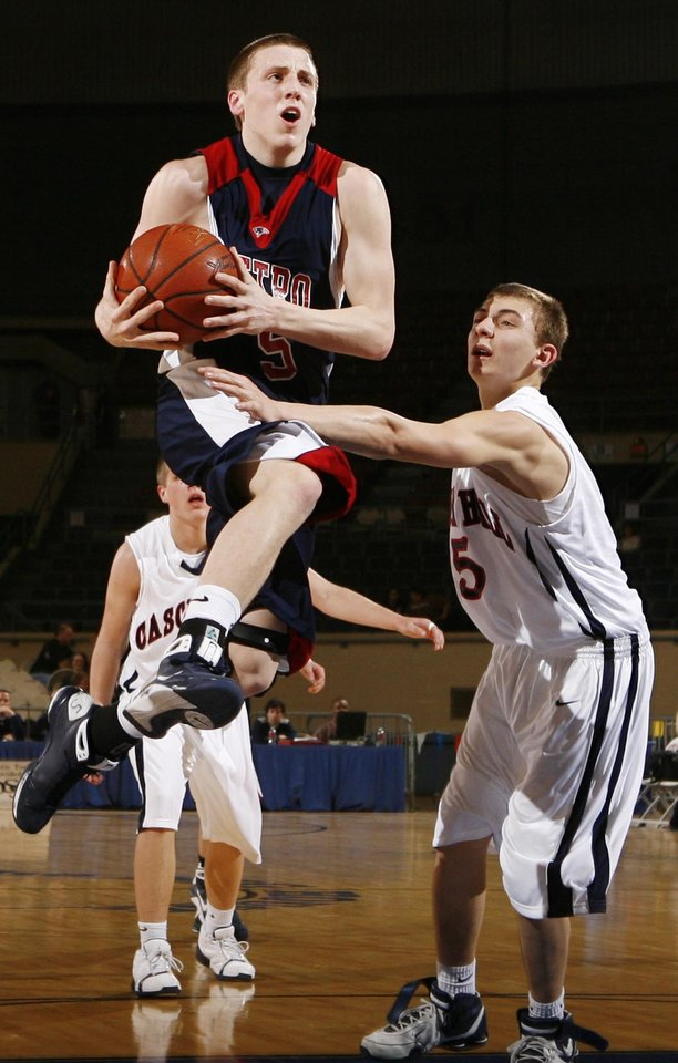 Photo - Metro Christian's Cliff Hughes (5) leaps past Matt Prueitt (5) of Cascia Hall during the 3A boys semifinal game between Metro Christian and Cascia Hall in the Oklahoma High School Basketball Championships at State Fair Arena in Oklahoma City, Friday, March 13, 2009. PHOTO BY NATE BILLINGS, THE OKLAHOMAN