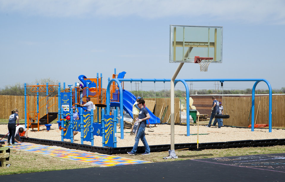 Photo -  Volunteers put finishing touches on the new Youth and Family Services playground in El Reno. PHOTO PROVIDED BY DEVON ENERGY