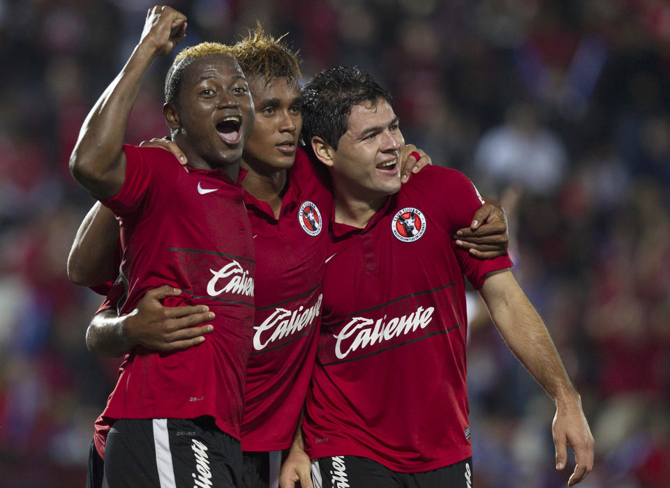 Tijuana's Pablo Aguilar, right, celebrates after scoring against Toluca with his teammates Duvier Riascos, left, and Fidel Martinez at a Mexican soccer league match in Tijuana, Mexico, Thursday, Nov. 29, 2012. (AP Photo/Christian Palma)