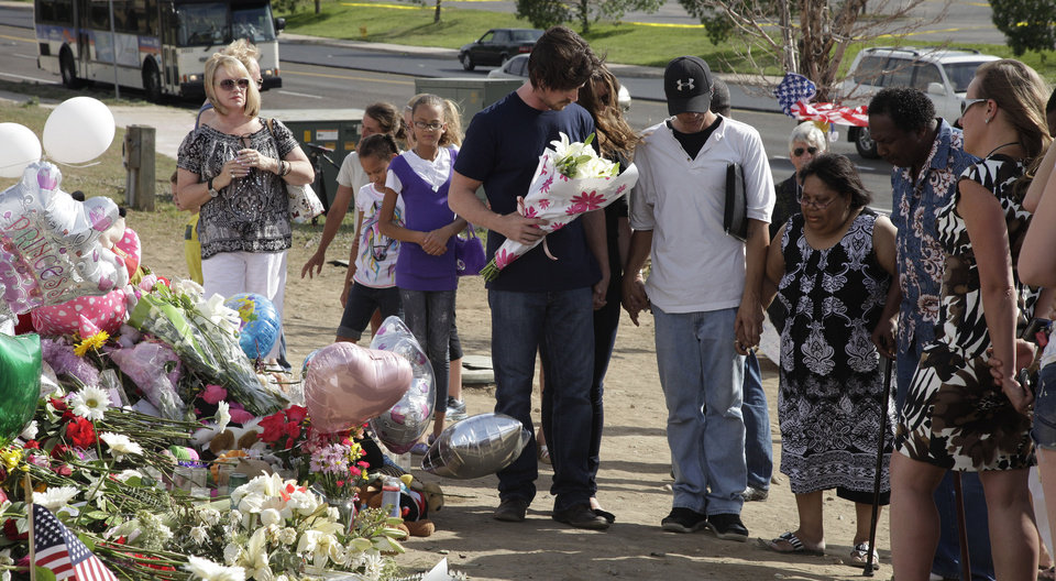 Photo -   Actor Christian Bale, holding flowers at center, joins hands and prays with visitors to a memorial to the victims of Friday's mass shooting, Tuesday, July 24, 2012, in Aurora, Colo. Twelve people were killed when a gunman opened fire during a late-night showing of the movie