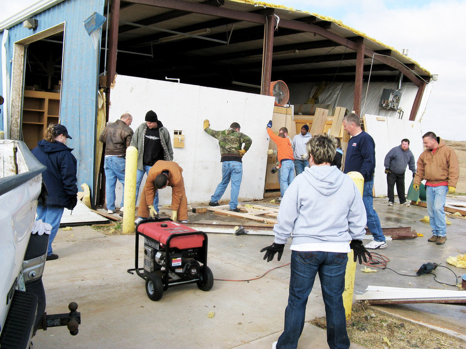 Photo - Workers erect a temporary wall to protect a cabinetry building business on Waterloo Road near Broadway. PHOTO BY SUSAN SIMPSON, THE OKLAHOMAN