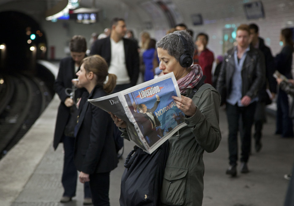 Photo -   A commuter reads a newspaper which fronts a picture of President-elect Francois Hollande in a Paris subway station Monday May 7, 2012. France handed the presidency Sunday to leftist Hollande, a champion of government stimulus programs who says the state should protect the downtrodden, a victory that could deal a death blow to the drive for austerity that has been the hallmark of Europe in recent years. (AP Photo/Peter Dejong)
