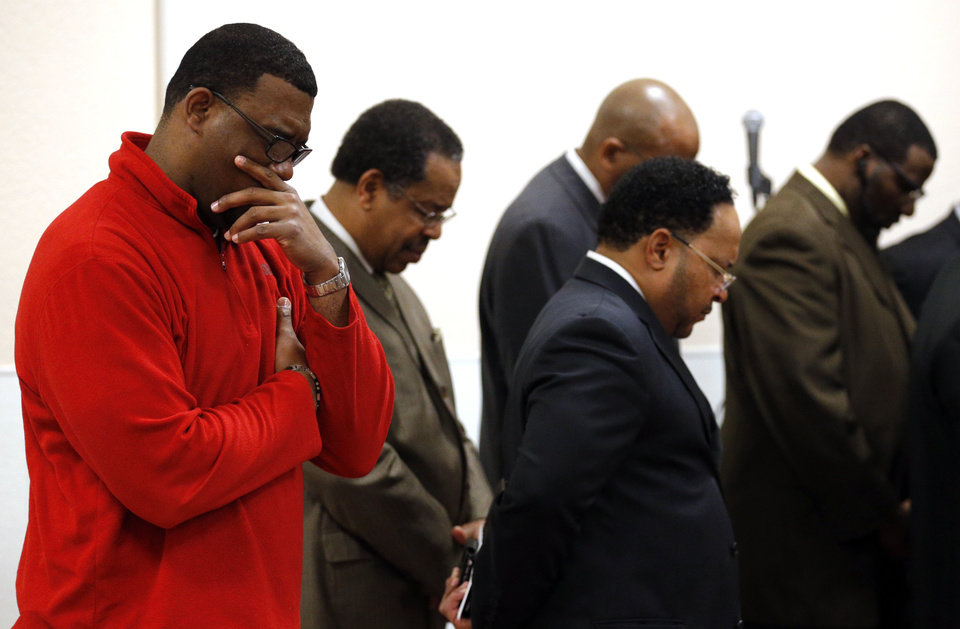 Photo - The Rev. Michael McDaniel with Northeast Missionary Baptist Church prays following a press at Fairview Baptist Church about the video incident involving Sigma Alpha Epsilon fraternity, Tuesday, March 10, 2015. Photo by Sarah Phipps, The Oklahoman