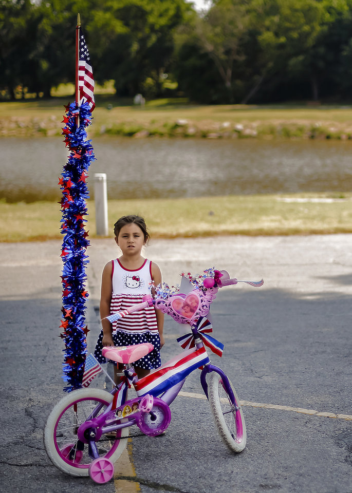 Meredith Malchaski, 4, of Yukon stands next to her bike as she prepares for the children\'s parade during the Yukon Freedom Fest at the Yukon City Park on Thursday , July 4, 2013, in Yukon, Okla. Photo by Chris Landsberger, The Oklahoman
